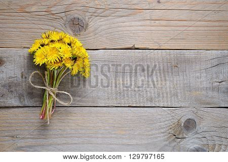 Bouquet of dandelion flowers on wooden background