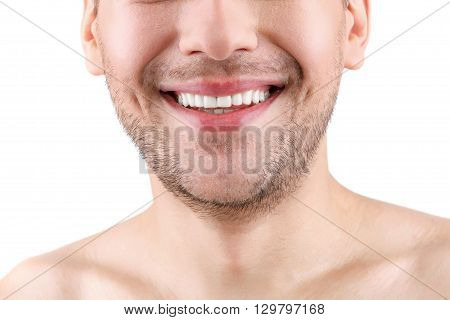 Close up of lower half of male face. The man is standing and smiling. He has stubble and naked shoulders. Isolated