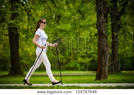 Nordic walking - middle-age woman working out in city park