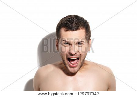 Portrait of young man shouting with anger. He is standing and looking forward with frustration
