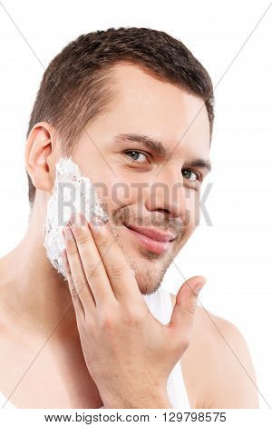 Portrait of handsome young man applying shaving foam on his face. He is standing and smiling. Isolated