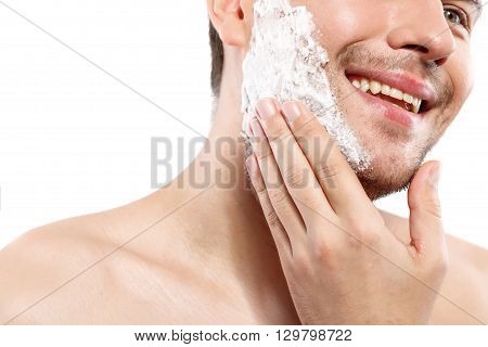 Cheerful young man is applying cream on his chin. He is ready to shave. Man is smiling. Isolated