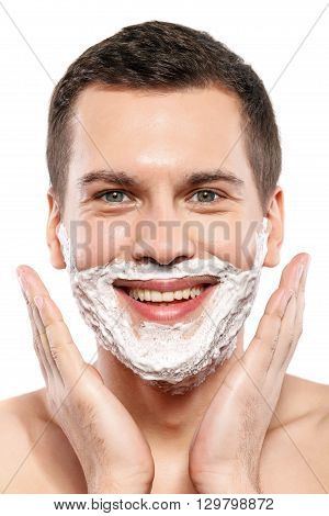 Portrait of attractive guy standing with shaving foam on his face. He is looking at camera and smiling. Isolated