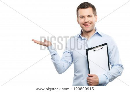 Waist up portrait of smart man presenting something with joy. He is standing and pointing arm sideways. Worker is holding a folder of documents and smiling. Isolated and copy space in left side