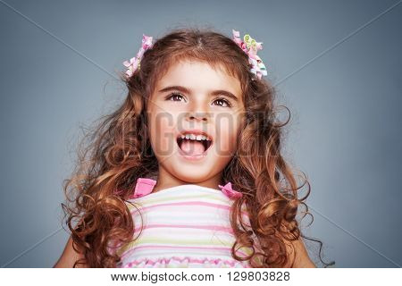 Portrait of a cute happy birthday baby girl,  beautiful child playing and making faces, shoot over sky background