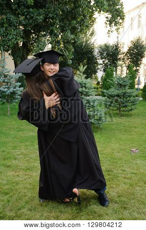 Graduate happily embracing his classmate. Student fun at his graduation ceremony