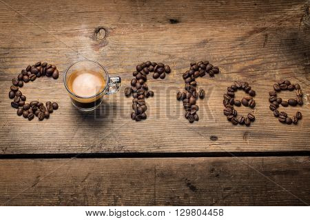 A transparent glass cup of hot steamy espresso standing on a wooden table top, surrounded by coffee beans spelling out the word coffee with the cup as the