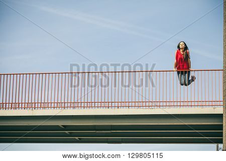 Young long haired girl leaning against railing on the urban bridge. Lifestyle funky in summer. Trendy sport teen jumping in air.