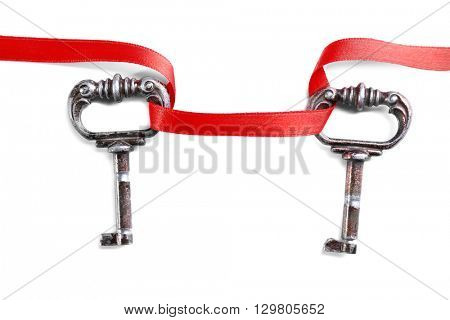Two vintage keys connected with a red ribbon on a white background