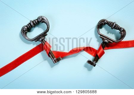Vintage key with  a red ribbon on a light blue background