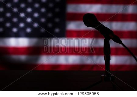 American flag in the darkness. Microphone and flag in darkness. Stage after the concert. Show has already ended.