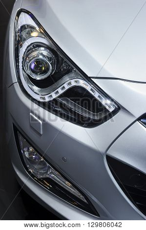 Сar headlight, hood and bumper with plastic air intake of powerful sports car with silver metallic glossy bodywork