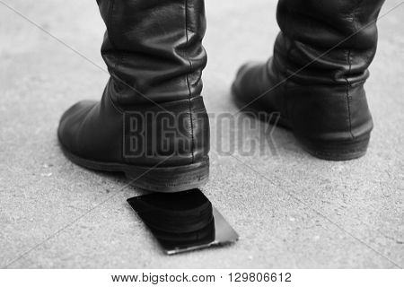 Female boots crushing a mobile phone on the pavement