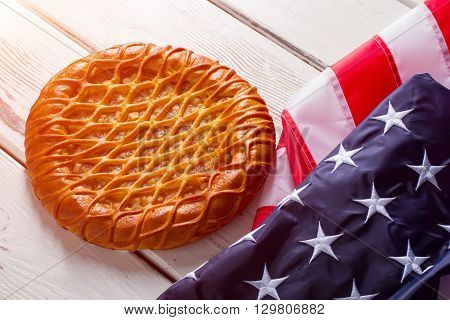 USA flag laying beside pie. Bakery product near bright banner. Traditional pastry on white table. Taste of patriotism.