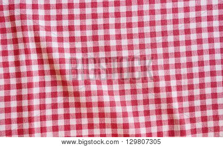 Red crumpled picnic tablecloth background. Red and white checkered fabric texture.