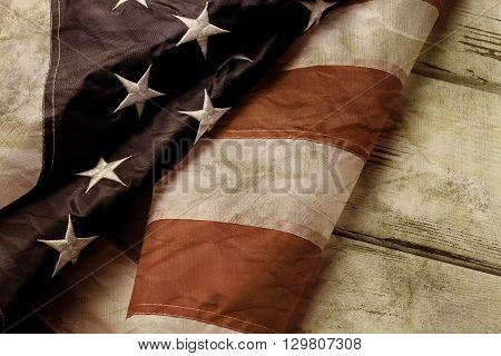 Old and crumpled american flag. Aged flag on wooden background. We've come a long way. Country with strong traditions.