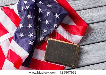US flag beside old book. Book laying on national flag. Constitution of United States. Strict laws guarantee safety.