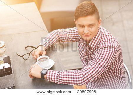 Handsome young man is drinking coffee in cafe. He is sitting at table and dreaming. Guy is looking forward with anticipation and smiling