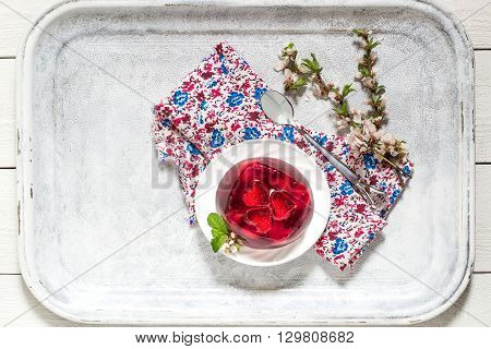 Delicious cherry jelly with whole berries on the plate and flowering branches of cherry on colored napkin and old white tray