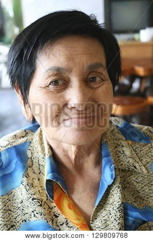 Asian old woman is smiling happily in the barber shop after dyeing hair done.