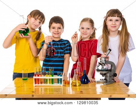 Four smiling kids holding a chemical flask, standing on the table with scientific equipment, isolated on white