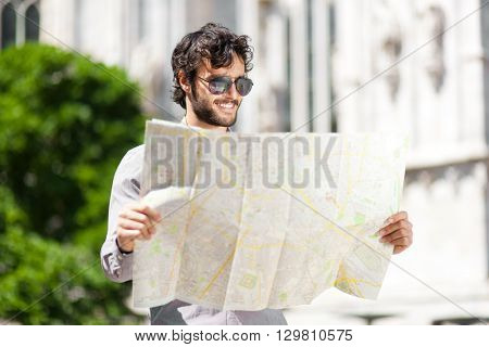 Young tourist in the city looking a map