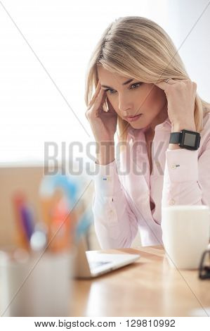 Attractive blond girl is working on a laptop. She is looking at screen with seriousness and touching her head. The lady is sitting at desk