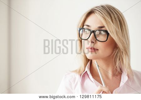 Pensive blond girl is standing and holding face near her face. She is looking aside and dreaming. The lady is wearing eyeglasses. Copy space in left side