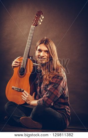 Music hobby concept. Smiled guitarist with his instrument. Young man is sitting on the floor with nice shirt and guitar.