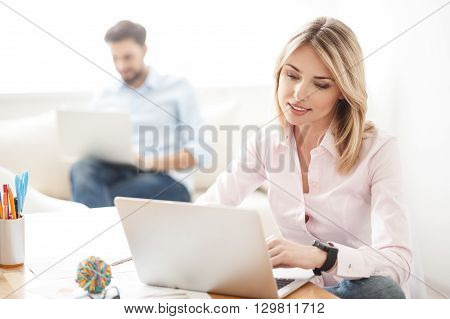 Attractive young businesswoman is typing on laptop and smiling. She is sitting at desk in office. Her male colleague is working on background