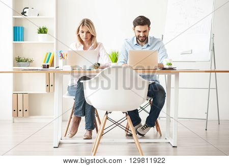 Full length portrait of skillful two colleagues typing on laptops and smiling. They are sitting at table in office