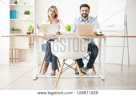 We like working together. Cheerful young business partners are using laptop in office. They are sitting at desk and looking at camera happily. Man and woman are smiling