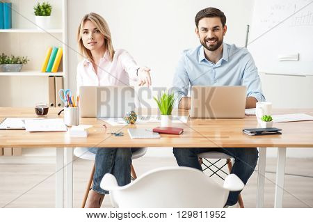Pretty creative team is inviting their client to sit down. They are sitting at desk and looking forward with joy. Man and woman are smiling
