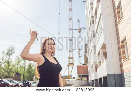 Beautiful smiling woman showing her new home keys against the backdrop of a house under construction.