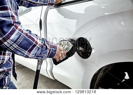 Mans Hand Holding Money While Refueling Vehicle