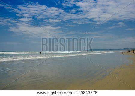 Muisne, Ecuador - March 16, 2016: Large beautiful untouched sandy beach by pacific ocean with small house construction, spectacular blue sky.