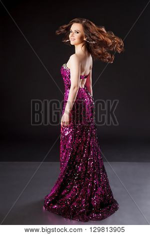 Portrait of women with flying wavy  hairstyle in evening dress with sequins. Black background