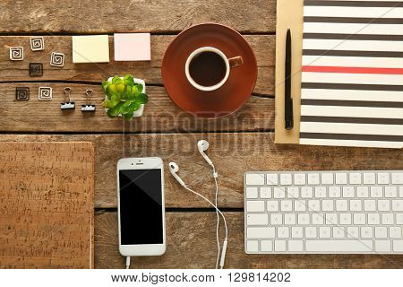 Workplace with mobile phone, keyboard and stationery on wooden table
