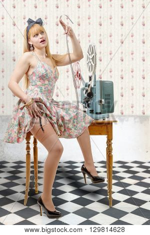 a sexy pin-up girl with a film reel and vintage film projector