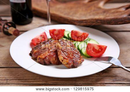 Roasted venison fillet and fresh vegetables on plate, on wooden background