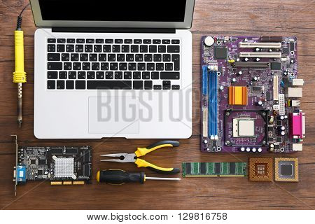 Laptop and different electronic circuits, tools on wooden table, top view