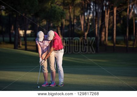 male golf instructor teaching female golf player, personal trainer giving lesson on golf course