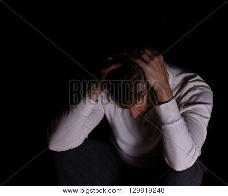 Depressed mature man holding head while looking down. Dark background.