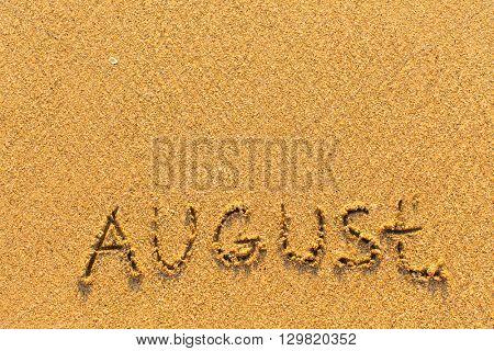 August - word inscription on the gold sand sea beach.