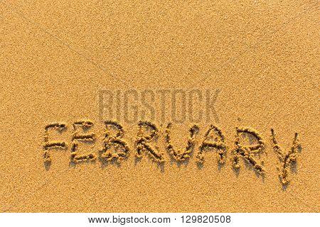February - word inscription on the gold sand sea beach.