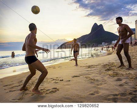 Rio de Janeiro, Brazil - December 19, 2015: Locals playing ball game at sunset in Ipanema beach, Rio de Janeiro, Brazil.