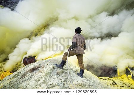 Kawah Ijen Volcano, East Java, Indonesia - May 25, 2013: Sulfur miner spraying water onto pipes inside the crater of Kawah Ijen volcano in East Java, Indonesia.