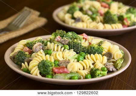 Pasta primavera with green asparagus pea broccoli mushroom and tomato in cream sauce served on plates photographed on dark wood with natural light (Selective Focus Focus in the middle of the pasta on the first plate)