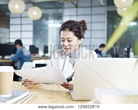 young asian business executive working in office looking at a report.