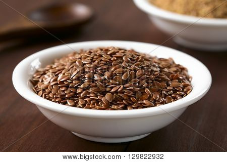 Brown flax seeds or linseeds in small bowl photographed on dark wood with natural light (Selective Focus Focus one third into the seeds)